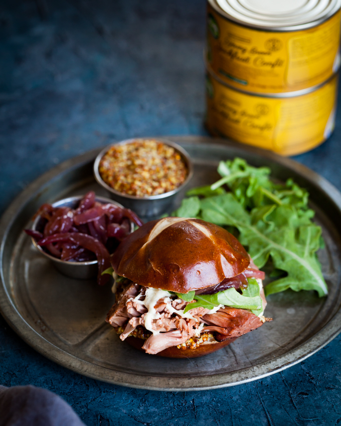This juicy Pub Style Jackfruit Confit Burger is ready in just 15 minutes, with quick-caramelized onions, melty vegan cheese, arugula, and spicy mustard on a pretzel bun. This easy, gluten-free sandwich is a must-try for dinner!